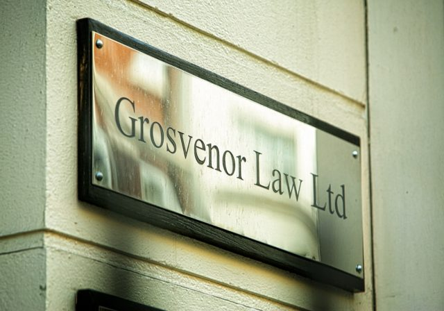 image of Grosvenor Law sign on wall outside office