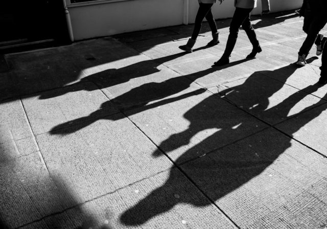 image of people walking and forming shadows on a street