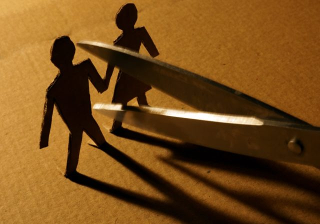 image of scissors cutting apart paper chain of two people to denote divorce