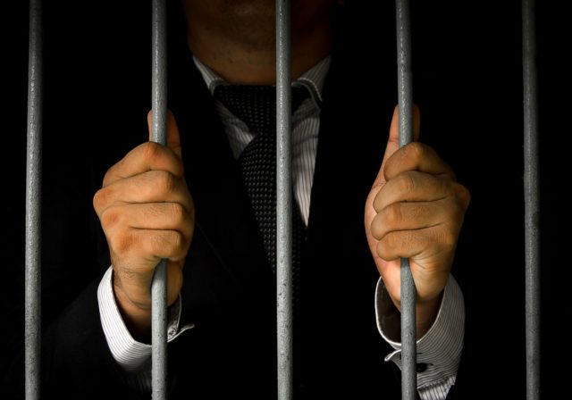 image of businessman behind bars to denote criminal liability