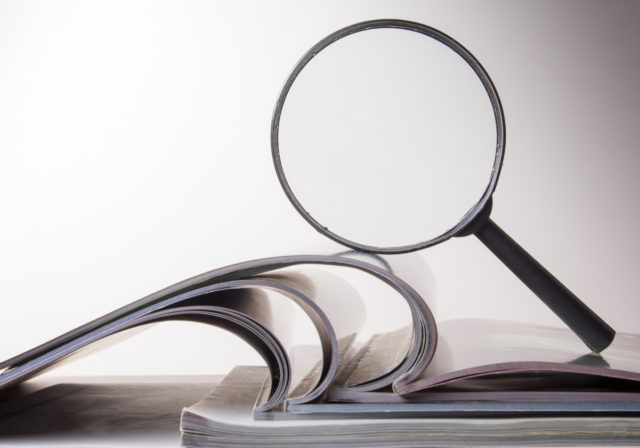 image of magnifying glass over book